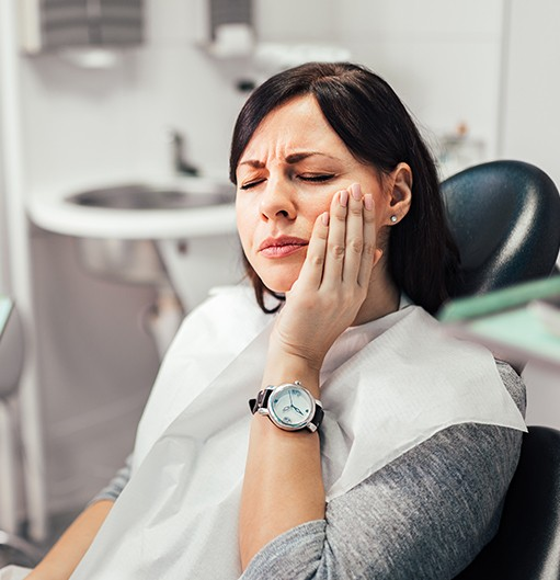 Woman in need of T M J therapy holding jaw